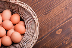 Brown eggs in a wicker basket brown table top view on the right Stock Photos