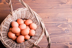 Brown eggs in a wicker basket with a handle on a brown table top Stock Image