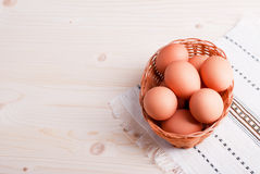 Brown eggs in a wicker basket on a light wooden table top view Stock Images