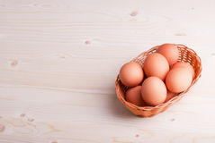 Brown eggs in a wicker basket on a light wooden table top view a Stock Photo