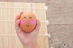 Brown-Eier mit glücklichem Gesicht in der Hand des Kindes Stockfoto