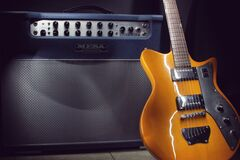 Brown Electric Guitar Beside Black Guitar Amplifier Stock Images