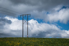 Brown Electrical Posts Surrounded With Green Grass Field Under Blue Sky and White Clouds during Daytime Royalty Free Stock Images