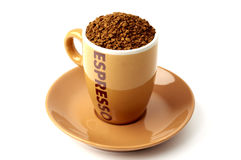 Brown elegant cup full of instant coffee granules, saucer under it. View from above, so it makes perfect round shape. Royalty Free Stock Photography