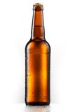 Brown entire bottle of beer with drops isolated on white Royalty Free Stock Photo