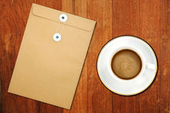 Brown Envelope document and a white coffee cup royalty free stock images