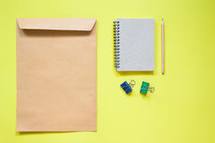 Brown envelope and notebook with stationery on yellow Stock Photos