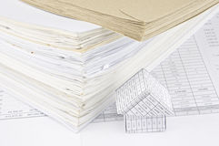 Brown envelope and overload of old paperwork with house Royalty Free Stock Photo