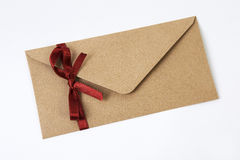 Brown envelope with red ribbon isolated on white Royalty Free Stock Photos