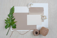 Brown envelope And writing paper. Dried flowers, leaves the putting green on a brown linen. Brown rolls with rope, Brown envelope And writing paper Stock Photos