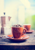 Brown espresso cup full of coffee beans on kitchen table with coffee pot Royalty Free Stock Photo