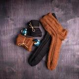 Brown et chaussettes et boules tricotées noires sur un noir et un fond gris photo libre de droits