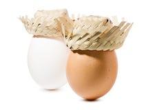 Brown et oeufs blancs avec le chapeau de paille d'isolement sur le fond blanc Image libre de droits