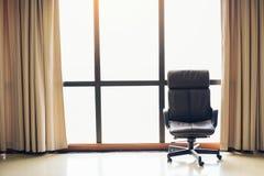 Brown-Exekutivlederstuhl in den leeren Büroräumen mit großem Fenster und drapieren lizenzfreie stockbilder