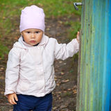 Brown eyed baby girl in pink hat opens gate Royalty Free Stock Image