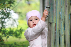 Brown eyed baby girl in pink plays with wicket Stock Photo