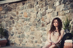 Brown-eyed brunette girl sitting on a bench Stock Images