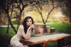 Brown-eyed brunette girl sitting on a bench Stock Photography