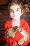 Brown-eyed girl with rabbit. I believe she is quite pleased with herself for being able to hold this rabbit royalty free stock image