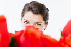 Brown eyes behind red roses. Brown eyes of a caucasian woman behind red roses - isolated on white Royalty Free Stock Photo