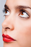 Brown eyes and red lips. Close up face portrait of a woman with big brown eyes and bright red lips royalty free stock photo