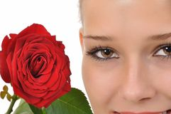 Brown eyes and a red rose. Close-up of a red rose and a young woman with brown eyes Stock Images