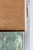 Brown fabric blinds on white plastic window Royalty Free Stock Images