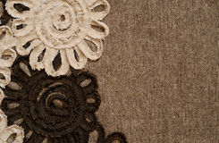 Brown fabric with flower edge. Background of brown fabric with ribbon flowers Stock Photos