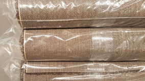 Brown fabric roll wrapped in plastic roll bag / stock of brown fabric for fashion design business Stock Photos
