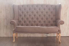 Brown fabric sofa in front of wooden wall. Close-up minimal shot Stock Image