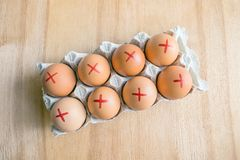 Brown farm eggs with red cross in white carton. Eggs recall over stock photo