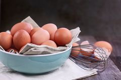 Free Range Brown Eggs. Brown farm fresh chicken eggs from free range chickens with whisk over a rustic wooden background Royalty Free Stock Photo