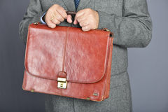 Brown fashion suitcase. Man, dressed in formal suite with elegant briefcase Stock Photography