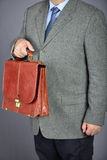 Brown fashion suitcase. Man, dressed in formal suite with elegant briefcase Stock Image