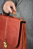 Brown fashion suitcase. Man, dressed in formal suite with elegant briefcase Royalty Free Stock Images