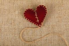 Brown felt craft heart over canvas close up Stock Photos