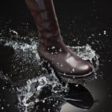 Brown female boot splashing water Royalty Free Stock Photo