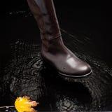 Brown female boot splashing water Stock Image
