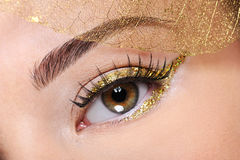 Brown female eye with a glamour golden make-up Royalty Free Stock Photo