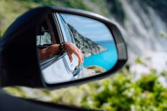 Brown female hand in the car side view mirror. Blue mediterranean sea and white rocks in background stock image
