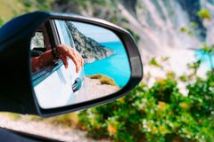 Brown female hand in the car side view mirror. Blue mediterranean sea and white rocks in background royalty free stock photos