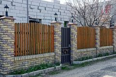 Brown fence made of bricks and wooden boards with a closed door. On the street royalty free stock photos
