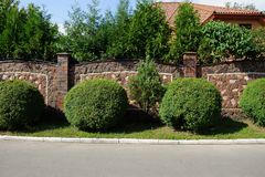 Brown fence of stones and bricks in the street with green bushes and grass royalty free stock photos