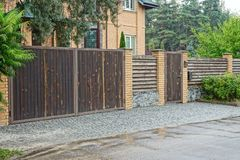 Brown fence and a wooden gate and a door on the street near the road. A private brown fence and a wooden gate and a door on the street near the road stock image