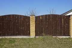 Brown fence of wooden planks and bricks in the green grass against the blue sky. Long brown fence of wooden planks and bricks in the green grass against the blue royalty free stock image