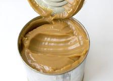 Brown ferveu o leite em uma lata de lata em um fundo branco foto de stock