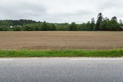 A brown field with ploughed rows of dirt next to a stripe of grass and an asphalt road Stock Photo