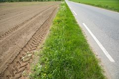 A brown field with ploughed rows of dirt with tractor tracks, next to grass and asphalt road royalty free stock photos