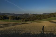 Brown field in sunset time with shadow of photographer. In spring time Royalty Free Stock Images