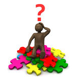 Brown figurine sitting on pieces of puzzle, asking Stock Photography